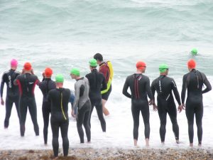 A group of swimmers in wet suits by the sea.