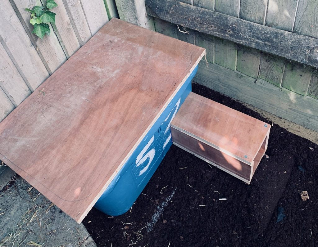 Photo of assembled hedgehog home made from a storage container and some wood