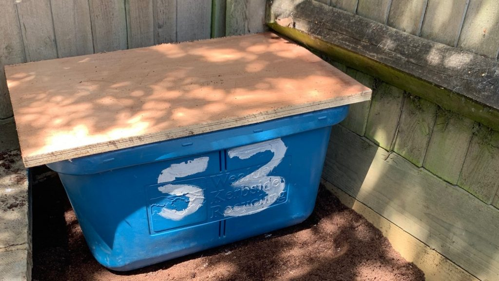 Photo of a plastic storage container with a piece of plywood on top as a lid