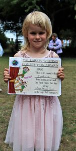 Isabella, one of the youngest winners at the award ceremony, stands proudly with her Val Larkin Award First Place Certificate.